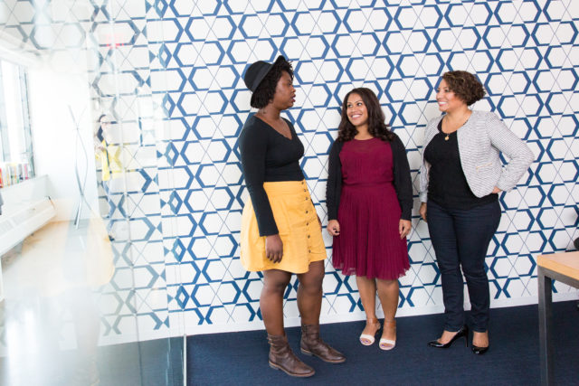 Three women stand in front of a blue and white wall
